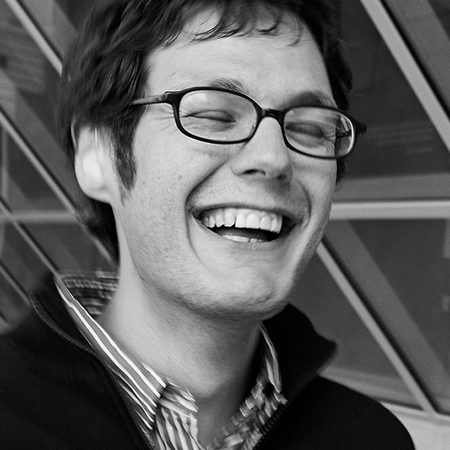 black and white photo of a young man wearing glasses 和 laughing