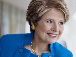 Woman with short blonde hair and blue suit smiling, with white background