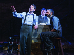 Three actors in period dress (suspenders, etc.) on stage pointing