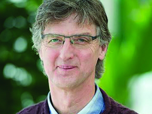 man with greying hair and glasses wearing a maroon sweater