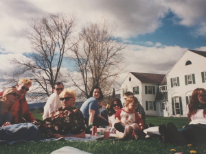 a group of students sit on a lawn with white houses in the background