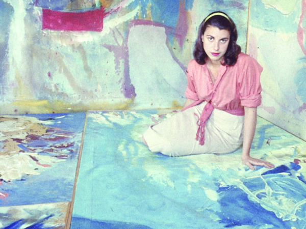 Young woman with brown hair, pink blouse and white skirt sits on a painting with paintings in background
