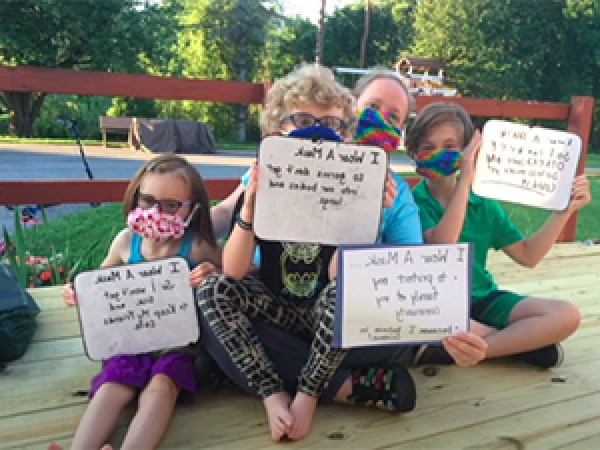 Image of family wearing masks and holding signs